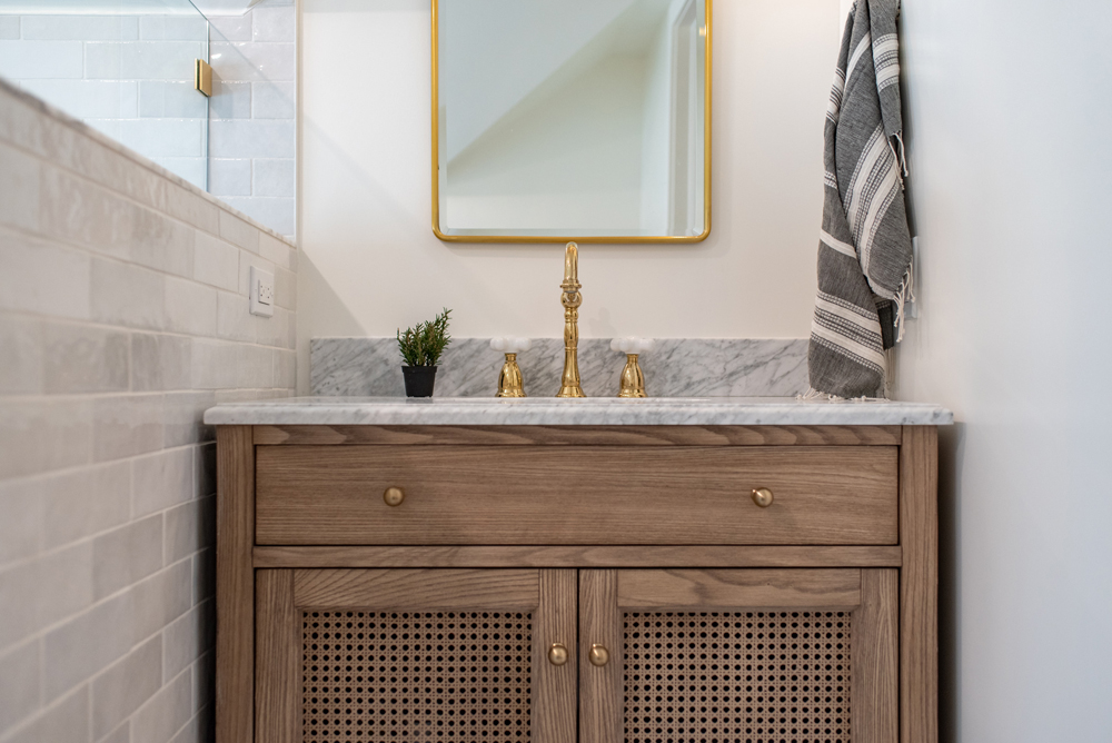Cane bathroom vanity with brass faucet