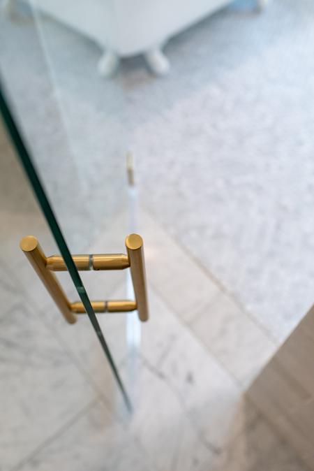 Glass shower door with brass handle
